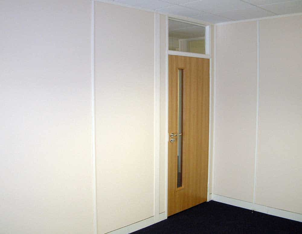 Solid full height partitioning with single door unit and glaze panel over